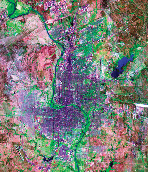Laredo, Texas (east of the Rio Grande river) and Nuevo Laredo, Taumalipas (west of the river). Blue, water; green, vegetation; blue-violet, roads and buildings; blue-violet areas on the western side of Nuevo Laredo, low-income neighborhoods; pink, land with little or no vegetation. (National Aeronautics and Space Administration (NASA)/U.S. Geological Survey LANDSAT 7 image [TM bands 7, 4, and 3];courtesy of NASA.)