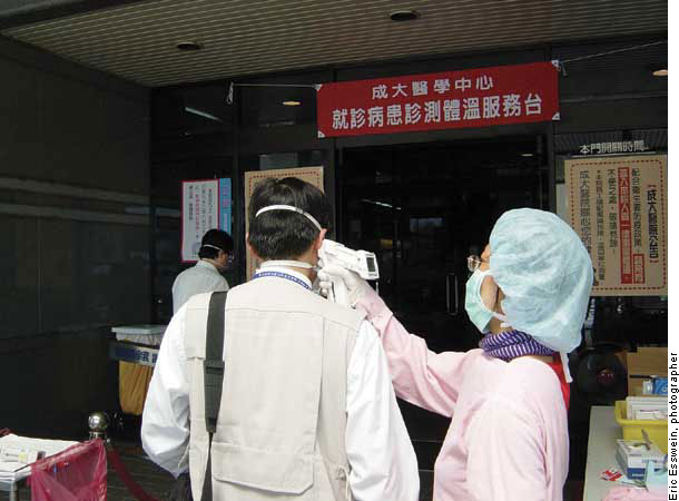 A Center for Disease Control Taiwan investigator is screened for fever before entering a healthcare facility in Kaohsiung. Photograph courtesy of Lukas Lee.
