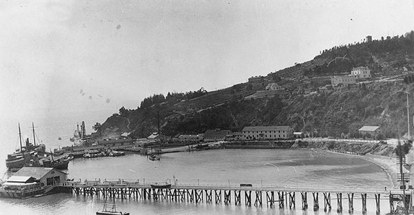 "Naval Training Station, San Francisco, California. View looking south over the wharf area, from the eastern end of Yerba Buena (""Goat"") Island, 1921. Long Wharf is in the foreground, lined with rowing boats on davits. Beyond is Navy Wharf, with the receiving ship Boston (1887–1946) at far left. The Lighthouse Wharf is beyond that. Collection of Eugene R. O'Brien. Photo #NH 100361. US Naval Historical Center photograph. From US Naval Historical Center (available from http://www.history.navy.mil/p"