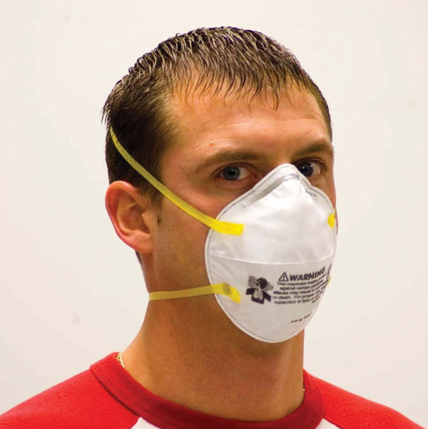 Properly donned disposable N95 filtering facepiece respirator. To be properly donned, the respirator must be correctly oriented on the face and held in position with both straps. The straps must be correctly placed, with the upper strap high on the head and the lower strap below the ears. For persons with long hair, the lower strap should be placed under (not over) the hair. The nose clip must be tightened to avoid gaps between the respirator and the skin. Facial hair should be removed before donning. Photo used with permission.