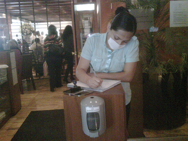 A reopened restaurant in Mexico City, Mexico, illustrating mask use by the person greeting entering customers and a hand hygiene dispenser that all entering customers were required to use, May 2009. Photo courtesy of Carlos del Rio.