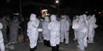 Thumbnail of Personal protective equipment worn by government workers assigned to cull poultry at a wet market in Huzhou city, Zhejiang Province, China, April 8, 2013. The protective clothing included ordinary disposable masks and latex gloves but not goggles or face shields.