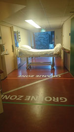 Thumbnail of Entrance of isolation unit with demarcated zones, Major Incident Hospital, University Medical Centre of Utrecht, the Netherlands, 2014. Markings on the floor indicate a safe zone and potentially contaminated zones and delineate doffing zones (where potentially contaminated clothing and gear are removed) for ambulance and disinfection personnel.