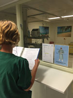 Thumbnail of A buddy nurse demonstrates reading instructions in front of the isolation unit glass window for healthcare personnel working inside the unit, Major Incident Hospital, University Medical Centre of Utrecht, the Netherlands, 2014.