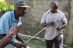 Thumbnail of A team consisting of workers from the US Centers of Disease Control and Prevention; the Pan American Health Organization; Haiti's Ministry of Agriculture, Natural Resources and Rural Development; and Christian Veterinary Mission trained 11 veterinary professionals on principles of animal rabies surveillance. Here, trainees gain experience drawing up sedative medications into a pole syringe, which is used to sedate suspected rabid animals from a safe distance. (Photograph courtesy of