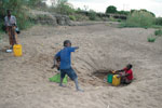 Thumbnail of A family searching for water by digging deep into a dried riverbed during the dry season in northeastern Zambia.