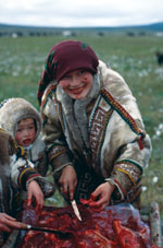 Thumbnail of A Khanty mother and her child eating raw reindeer meat in the Yamal Peninsula (Yamalo-Nenets Autonomous Okrug), northern Siberia, Russia, 1991. Photograph courtesy of Marianna Flinckenberg-Gluschkoff.