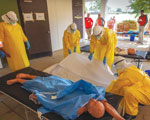 Thumbnail of Constructed mock Ebola Treatment Unit used during the Centers for Disease Control and Prevention Ebola Safety Training Course, held at the US Federal Emergency Management Agency Center for Domestic Preparedness in Anniston, Alabama, USA, 2014–2015. Trainees prepare to place a simulated deceased patient into a body bag.