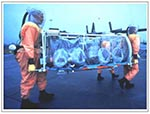 Thumbnail of Aeromedical isolation team members in field-protective suits equipped with battery-powered HEPA-filtered respirators transporting the stretcher isolator, a light-weight unit designed for initial patient retrieval. The team trains on several types of military aircraft, including the C-130 transport shown in the background.