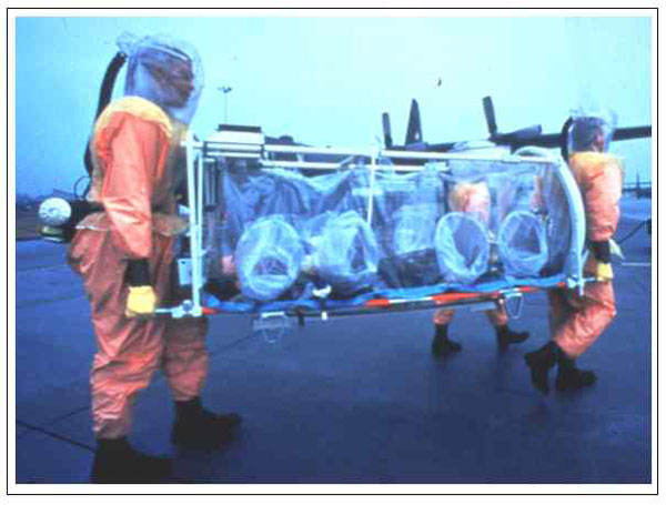 Aeromedical isolation team members in field-protective suits equipped with battery-powered HEPA-filtered respirators transporting the stretcher isolator, a light-weight unit designed for initial patient retrieval. The team trains on several types of military aircraft, including the C-130 transport shown in the background.