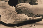Thumbnail of This historic 1975 photograph shows a laboratory technician preparing doses of polio vaccine by placing a liquid droplet of the vaccine upon each of these sugar cubes, which would subsequently be ingested orally by each recipient. Photo: Public Health Image Library, CDC, 1975
