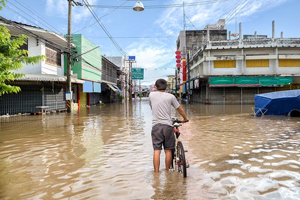 man walking bike through floodwaters
