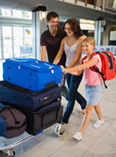 Family walking through airport with luggage