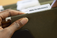 Hand with health insurance folder