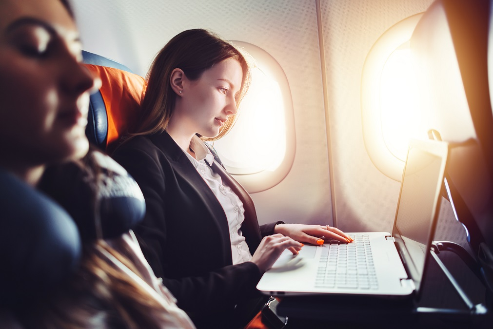 Business traveler working on laptop on airplane