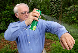 man spraying insect repellent
