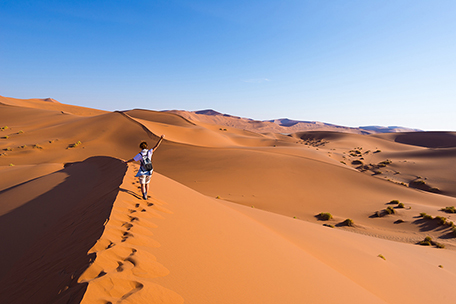 Woman walking on sand dunes