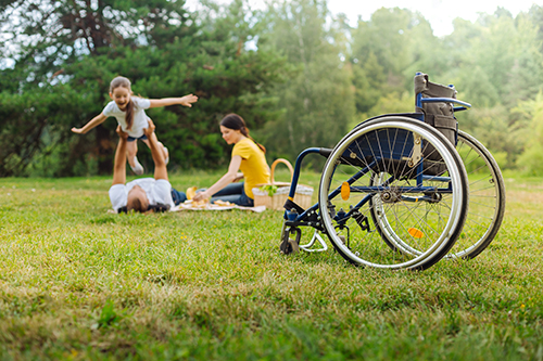wheelchair in park, people in background playing